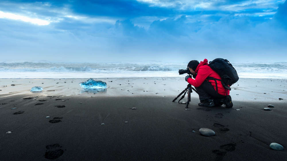 Photographer taking a shot of a beautiful black sand beach in Iceland