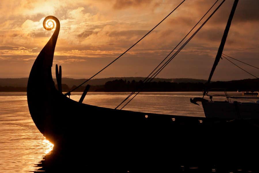 Barco vikingo a contraluz en un precioso atandecer