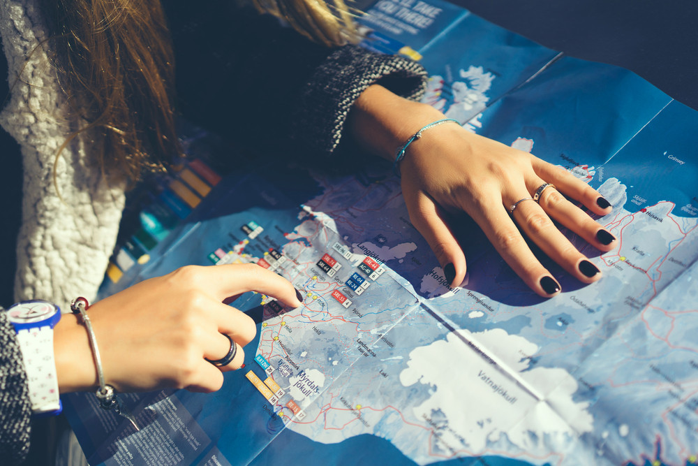 Girl checking her route in a map for her day tour in Iceland