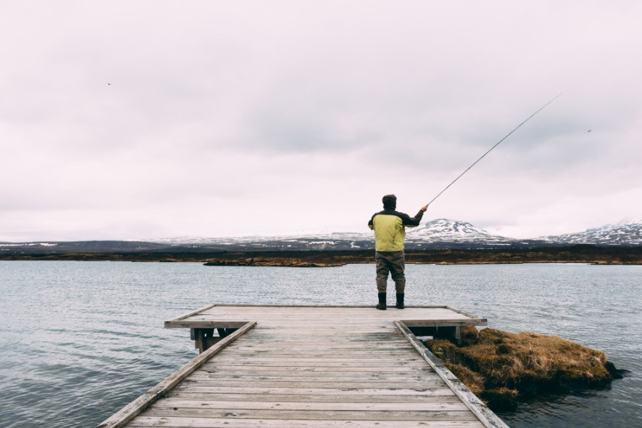 man fishing in Iceland by the fjords