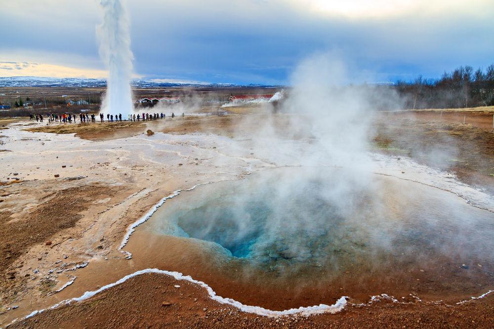 Geysir erupcionando junto a una zona geotermal con turistas