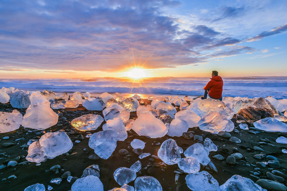 tourist at the diamond beach enjoying the sunset - best time to visit iceland
