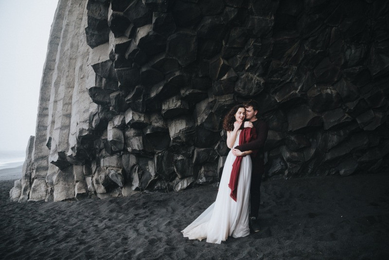 Groom and bride at the black sand beach of Iceland