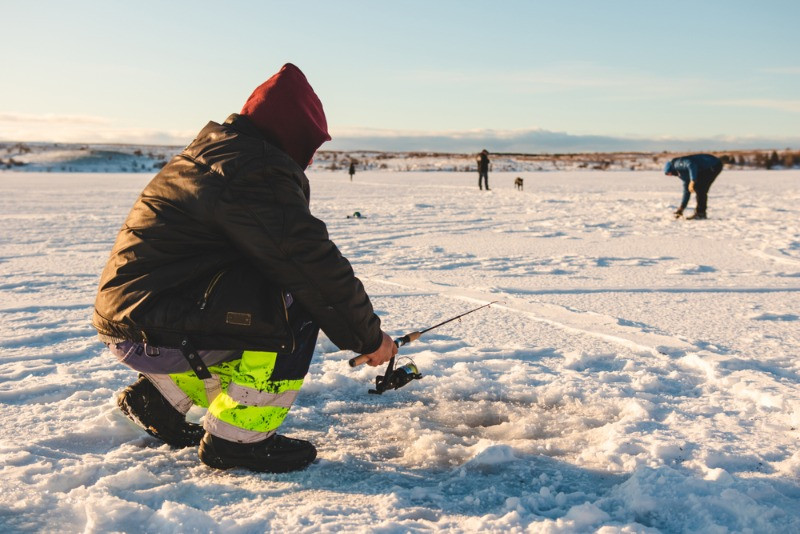 people practising ice fishing in Iceland