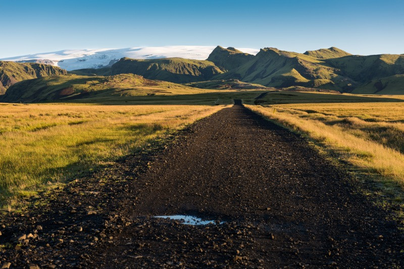 Carretera de grava que lleva a un glaciar Islandés rodeado de montañas