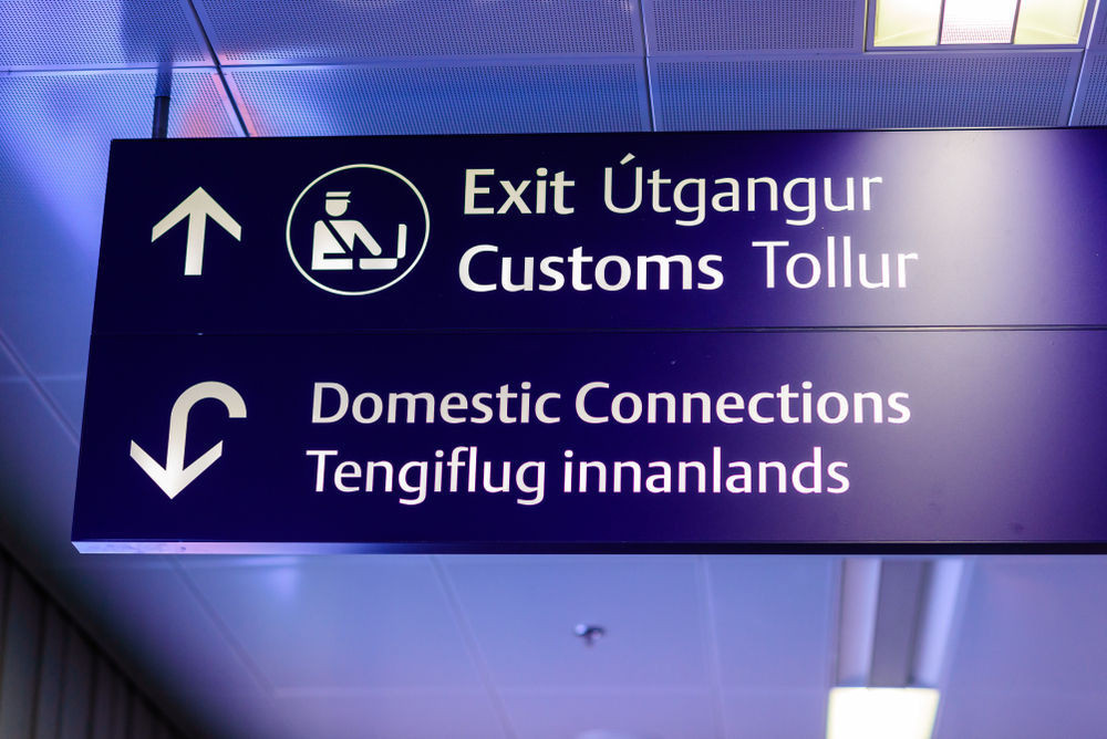 Airport sign showing the way to customs and domestic connections- flights to Iceland