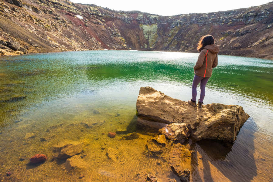 Joven visitando la laguna del lago de Kerid de cerca