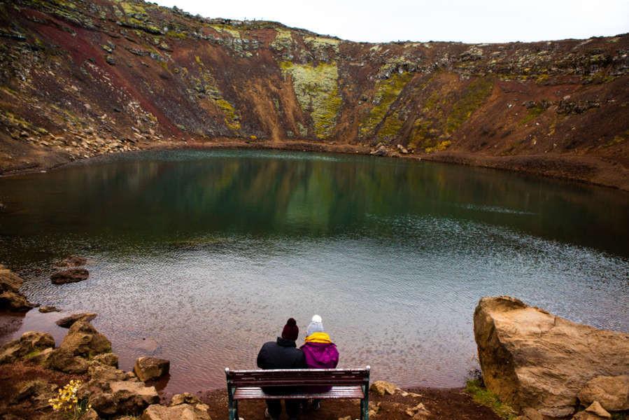 Pareja sentada en un banco disfrutando de las vistas del lago Kerid