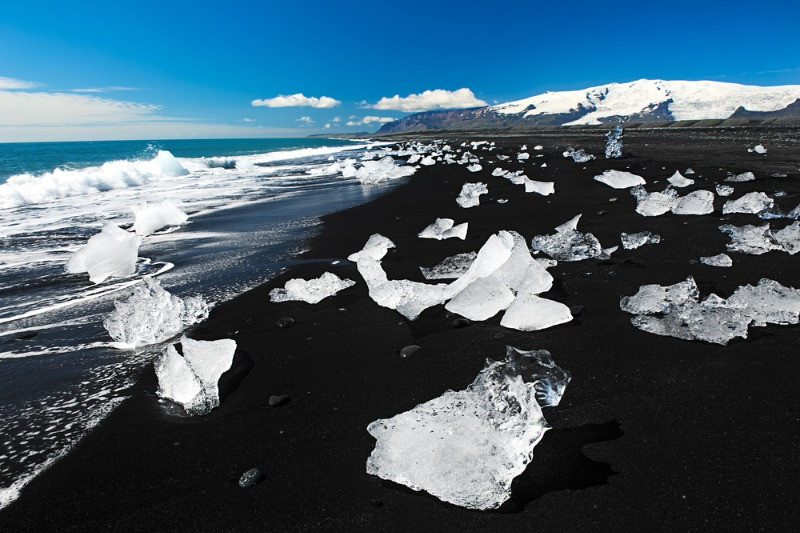 Ice pieces scattered on a black sand beach