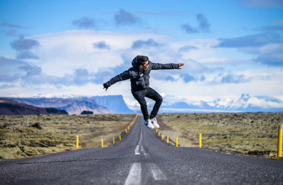 young man jumping in the middle of an Icelandic road