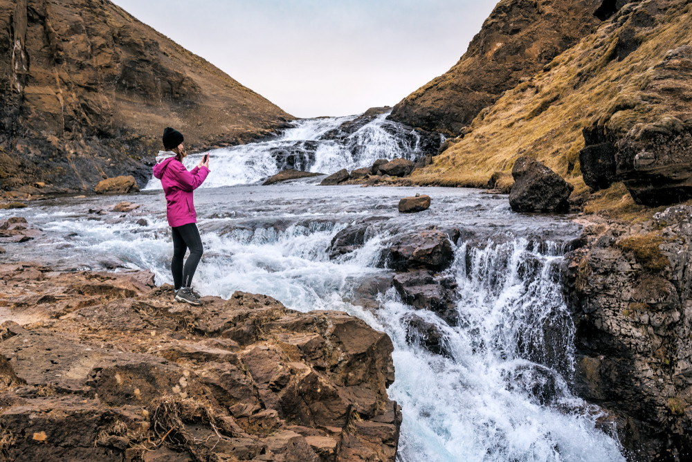 girl taking a picture of Glymur waterfall, another important waterfall besides Seljalandsfoss