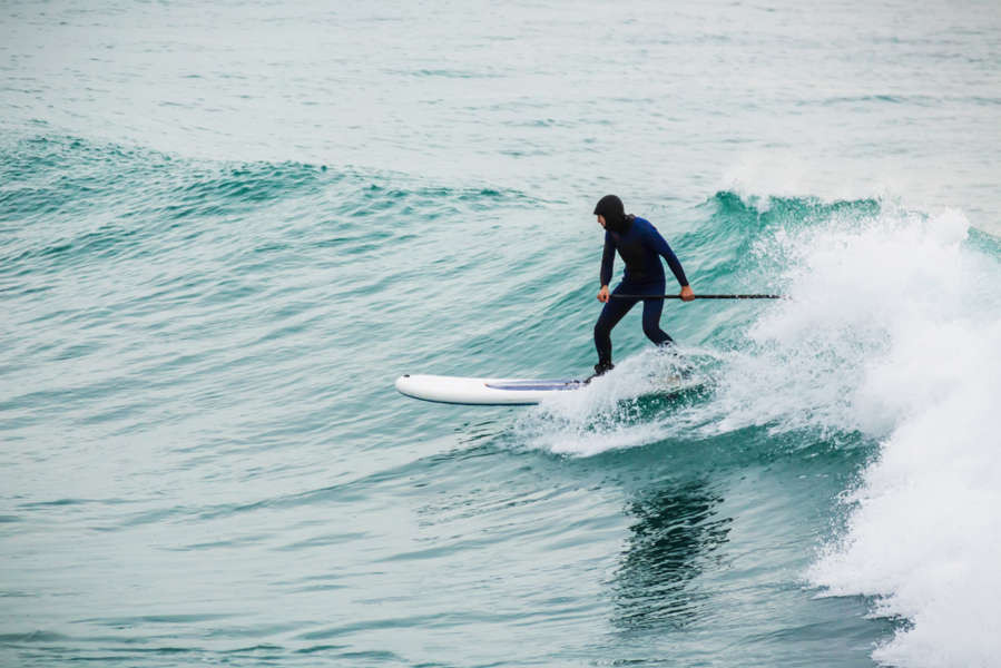 young man surfing in Iceland and riding the waves