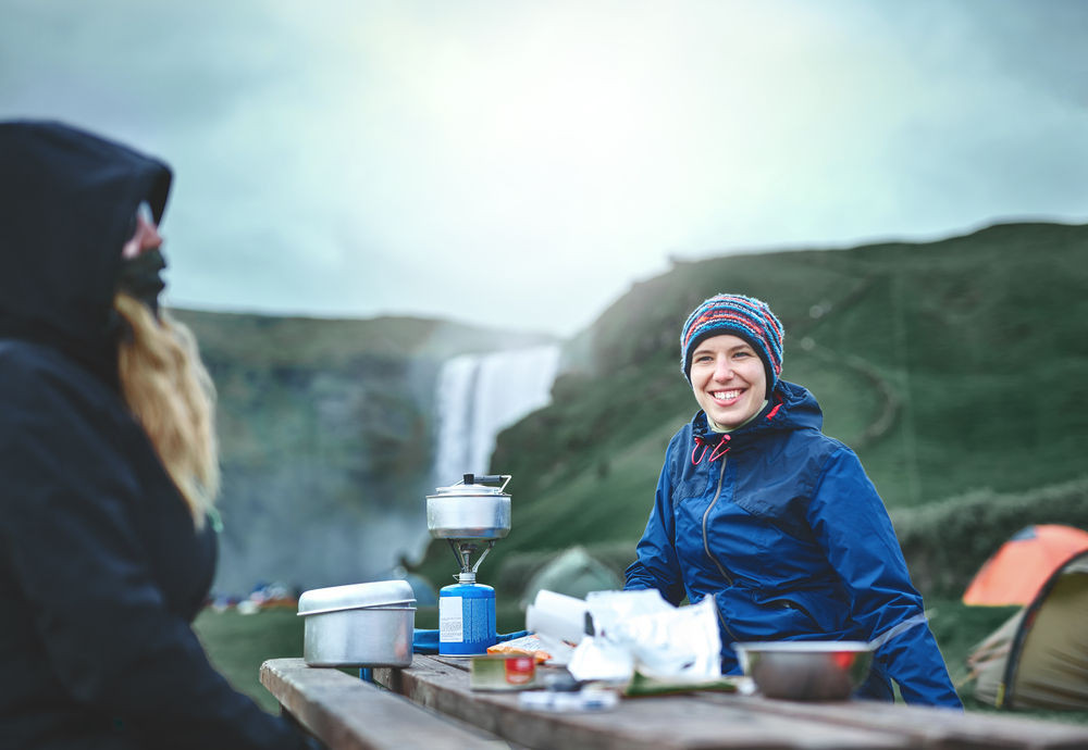 Two young women camping in Iceland preparing their food