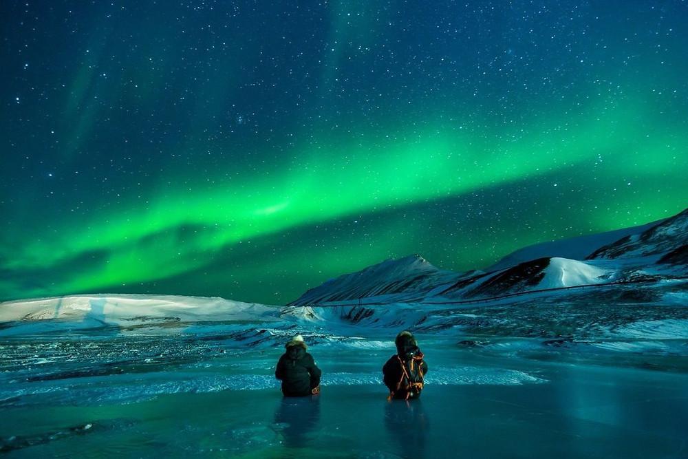 Dos turistas disfrutando de las auroras boreales con temperaturas bajas en reikiavik
