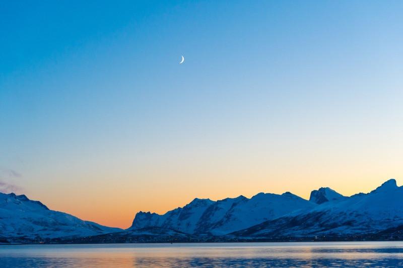 Panorámica del sol de medianoche en Islandia junto con la luna en el cielo.