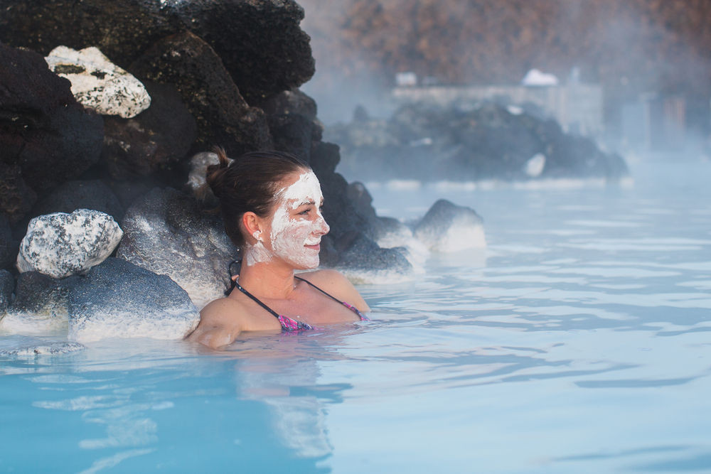 woman with a silica mud mask on her face in the waters of the Blue Lagoon
