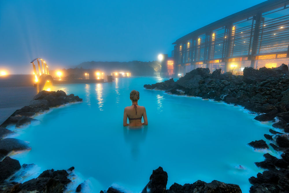Woman enjoying the Blue Lagoon in Iceland at night
