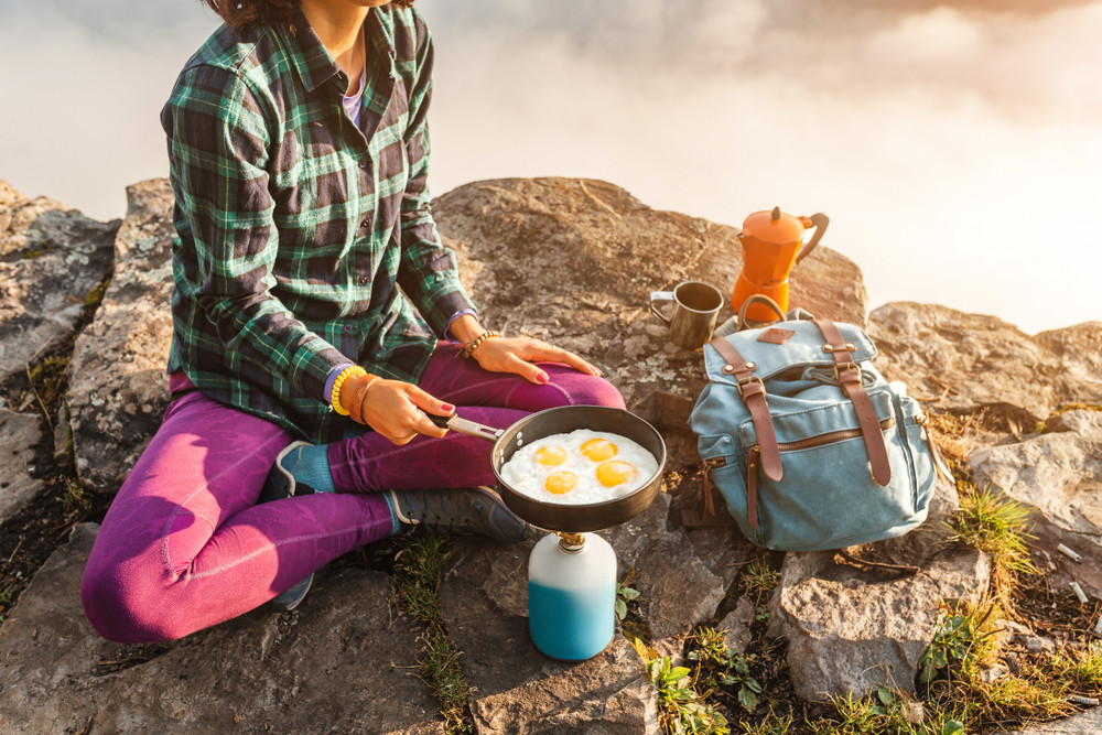 woman cooking her own food to avoid extra cost and make camping easy in Iceland