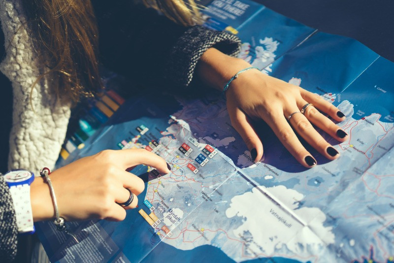 Girl with a map checking her ring road in Iceland itinerary