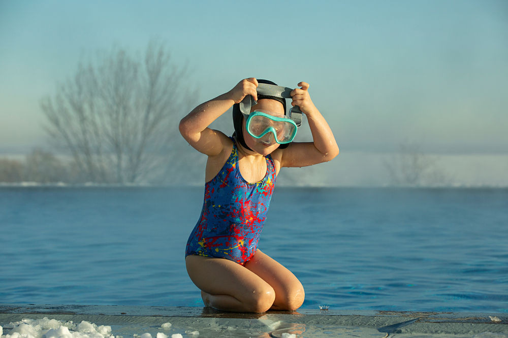 Child putting her goggles on to swim at Reykjavik's pool
