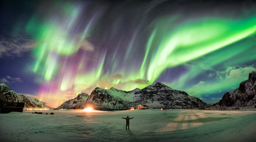 turista che gode dell'aurora boreale in Islanda