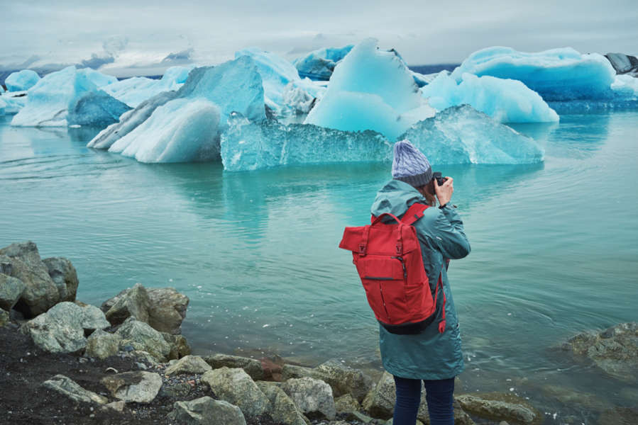 Young woman taking a picture of the icebergs at Jokulsarlon glacier lagoon