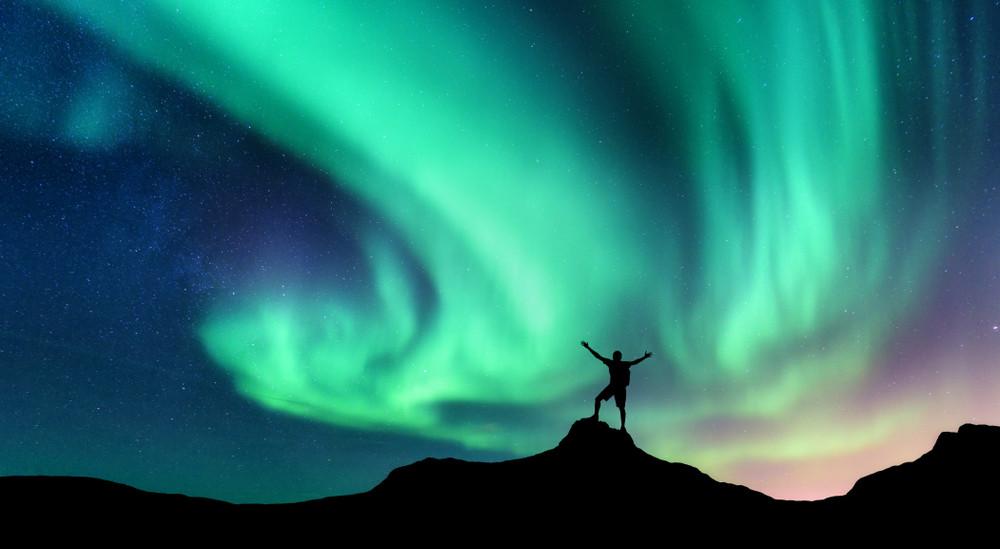 turista con las auroras boreales en Islandia de fondo