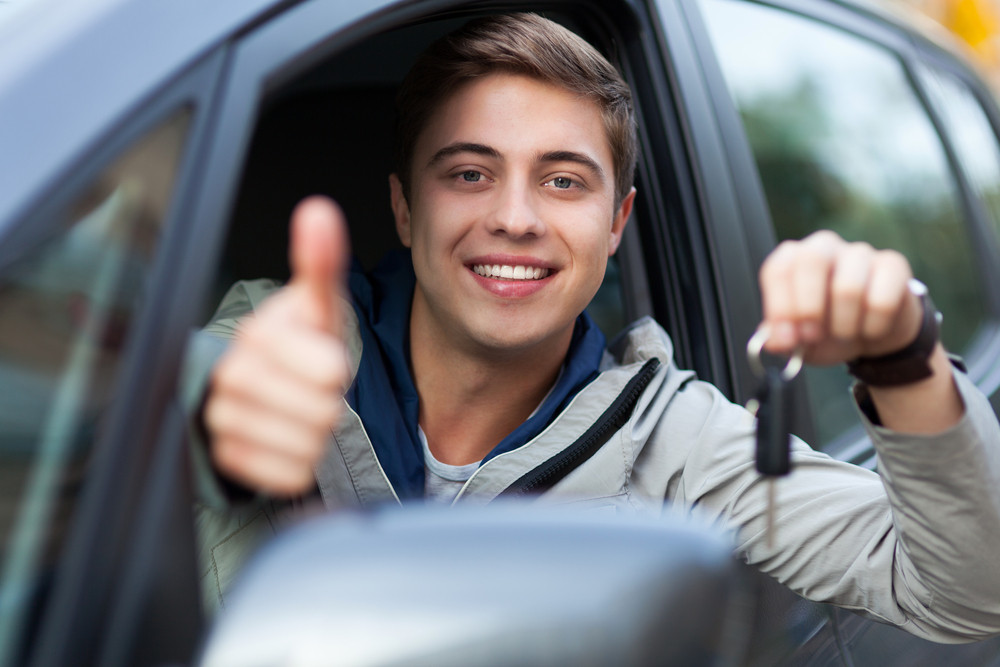 young man holding his rental car keys as he meets the minimum driving age in Iceland