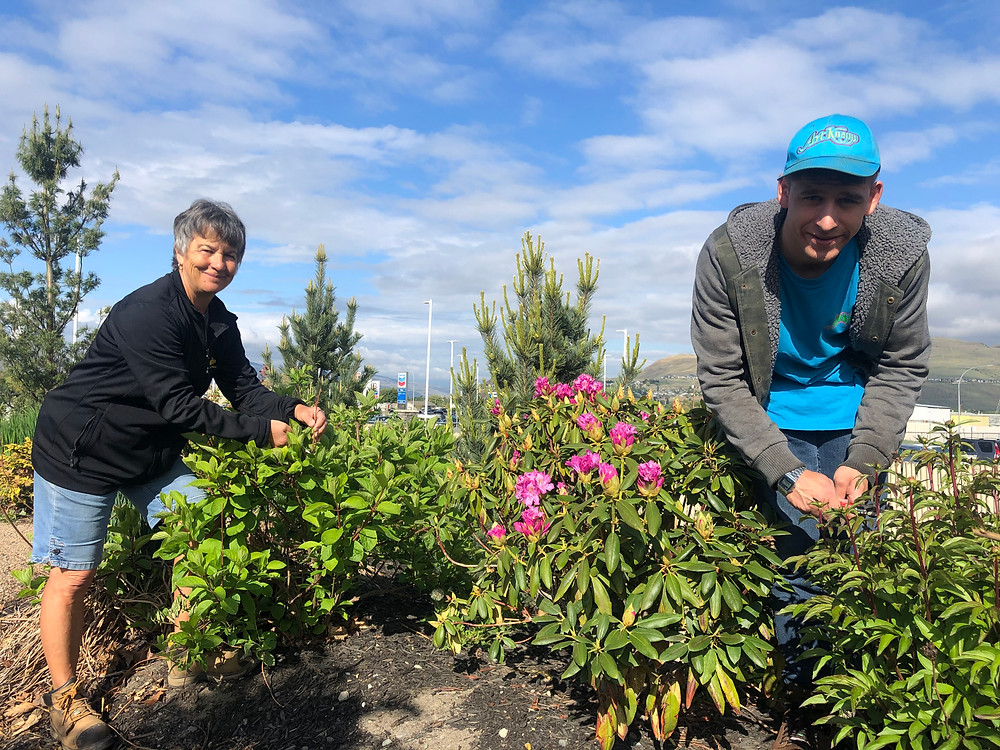 Two employees who were connected with Kamloops employers with the help of SMART Options working out in a garden.