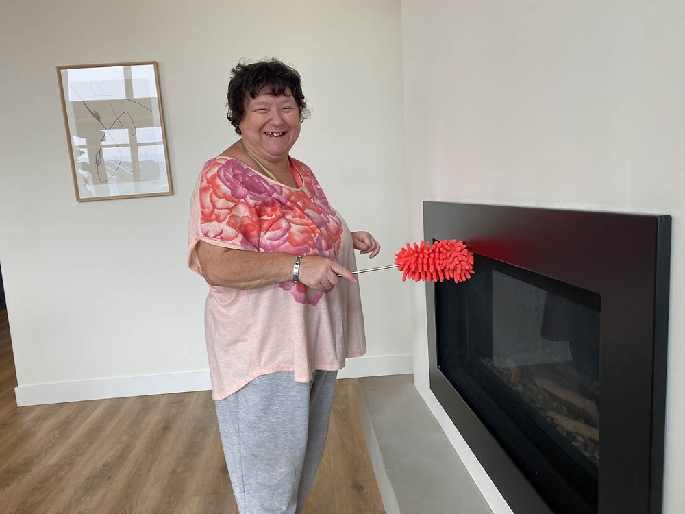 Dawn smiles and cleans a fireplace with a duster as part of her developmental disability employment program with SMART Options in Kamloops.