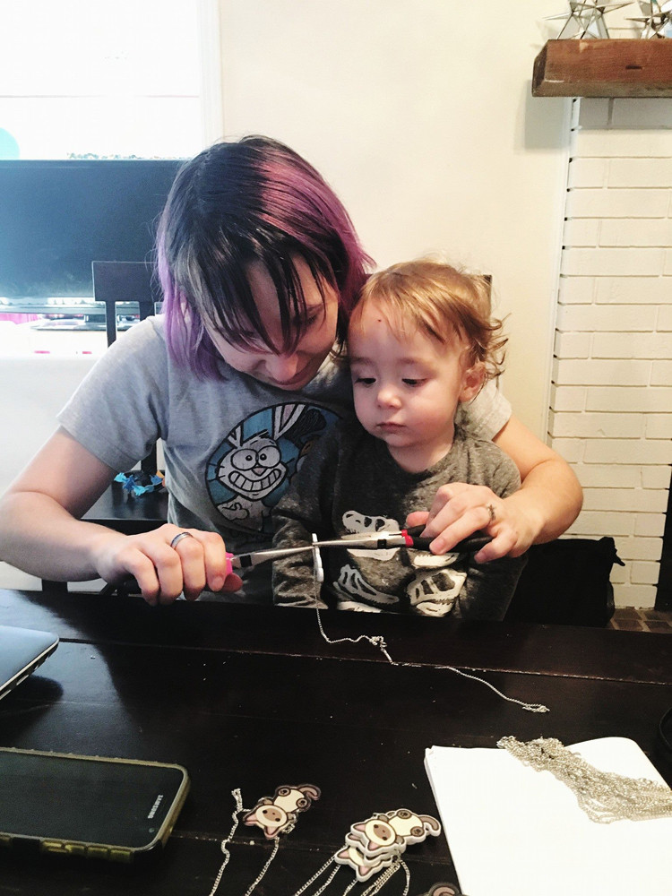 Photo of toddler on mom's lap while she is crafting