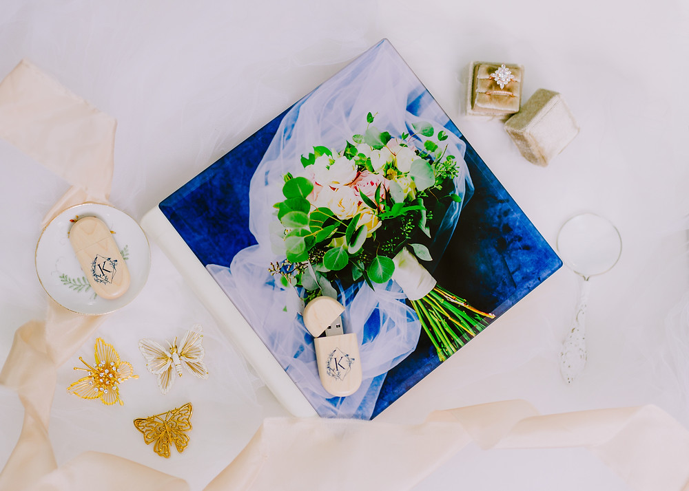 Flatlay image of a wedding album, butterflies and usb drives