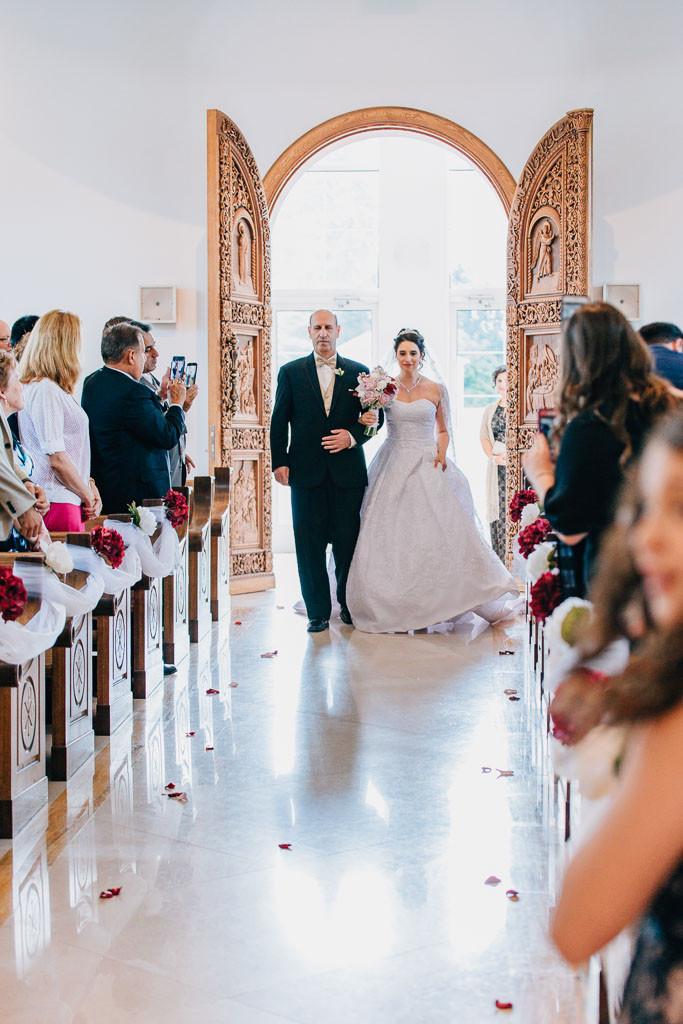 bride coming down the aisle with her father