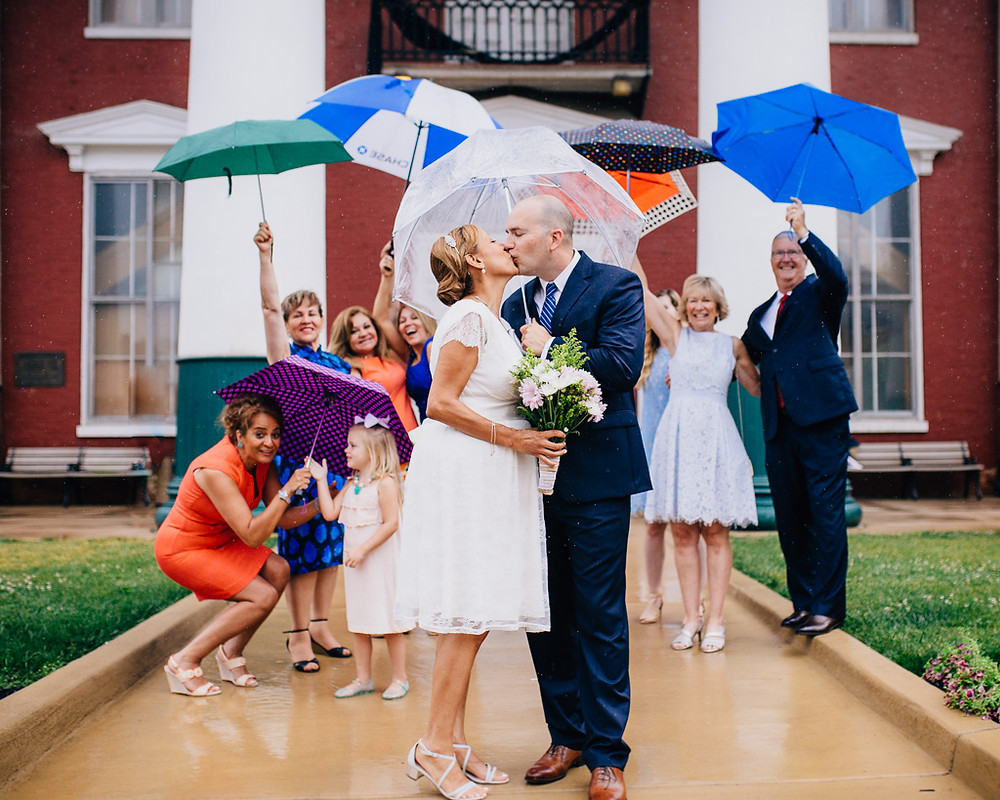 friends cheering rainy day wedding colorful umbrellas