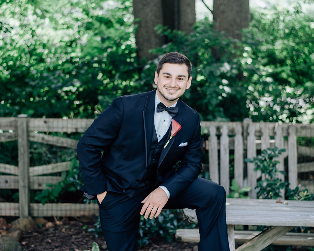 casual groom in tux in back yard