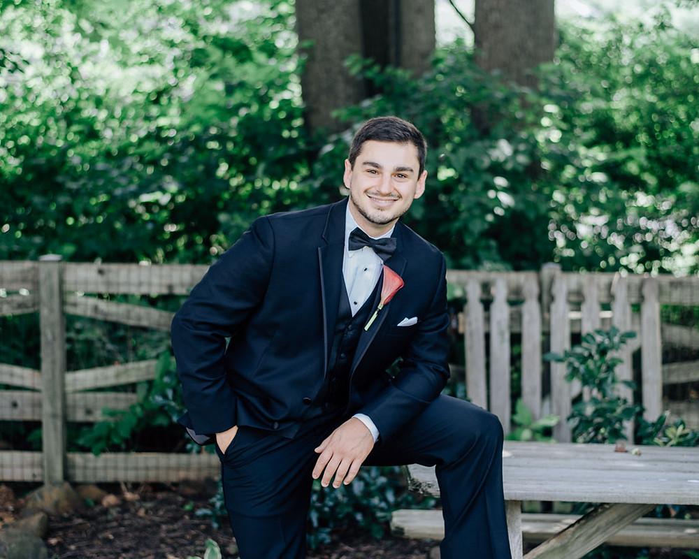 casual groom in tux in back yard