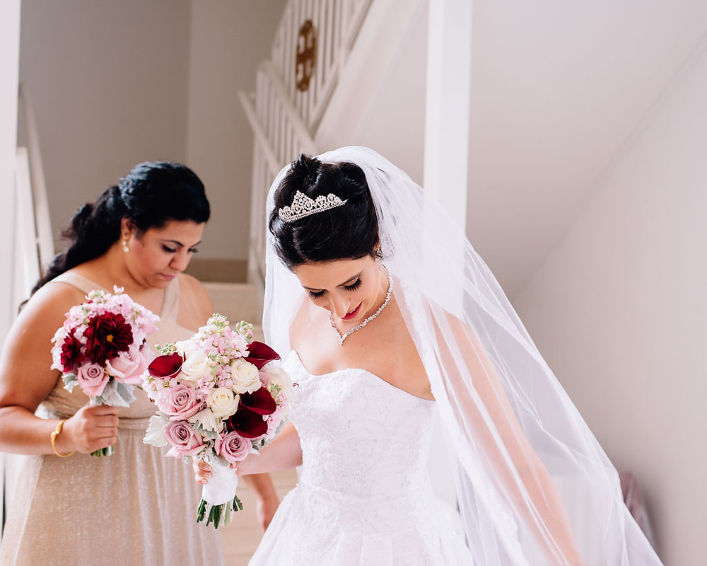 bride adjusting her veil with pink and burgundy bouquet
