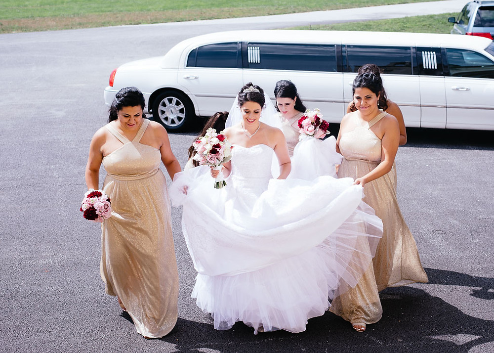 bridesmaids helping bride with limo