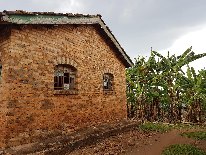 Typisches Backsteinhaus, in Hintergrund Bananenstauden