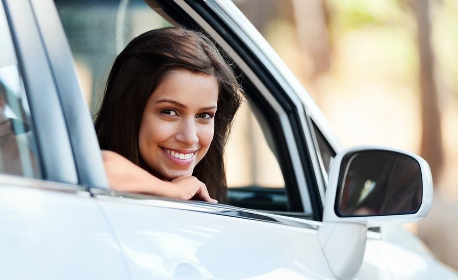 learner driver smiling and looking out of car window