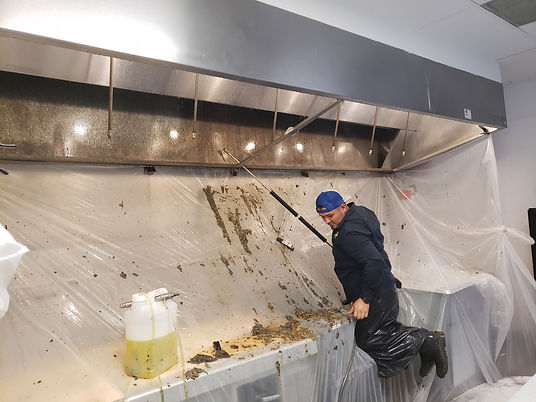 Cornerstone Commercial Services employee cleaning a dirty vent hood exhaust system.