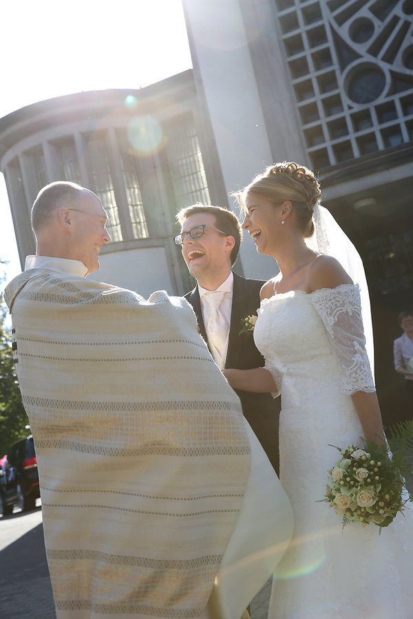 Foto von Brautpaar und Pfarrer nach der Trauung nach dem Auszug aus der Kirche
