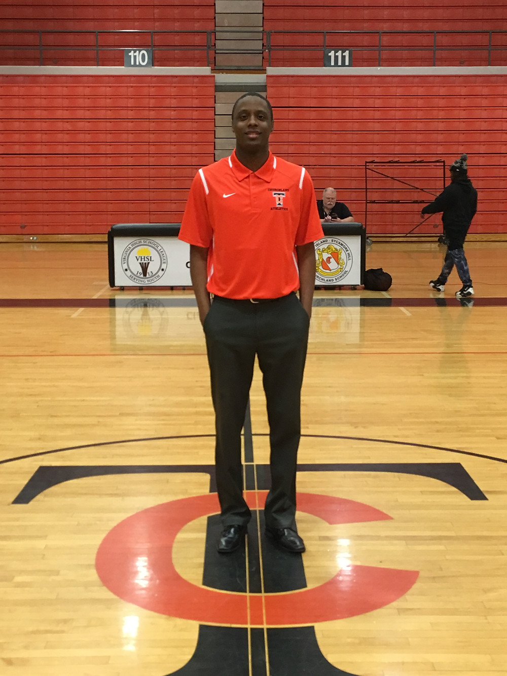 Coach Green standing in the center of the Churchland High School basketball court.