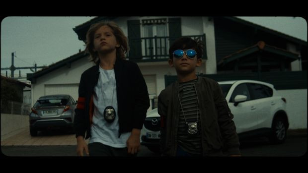 Two 8-year-old boys, one with sunglasses, walking away from a house
