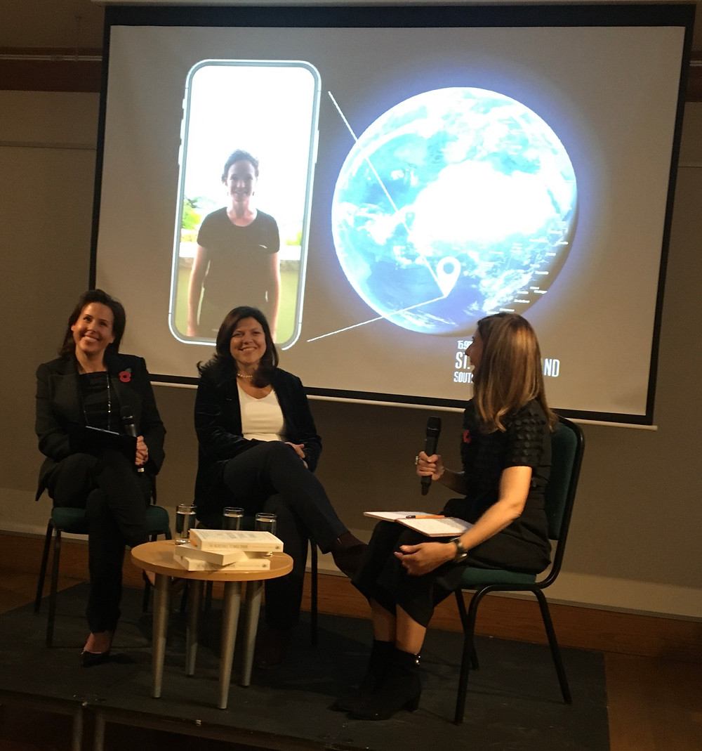 Two authors sitting with the woman interviewing them with a picture of the third author on a screen behind them