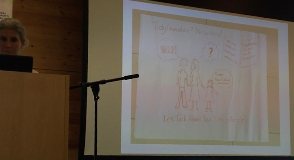 "Lucy Emmerson standing near a microphone next to a drawing that says ""tricky conversations"""