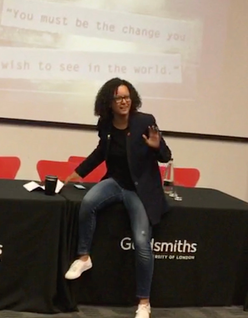 Mandu Reid sitting on the edge of a table with her hand in the air