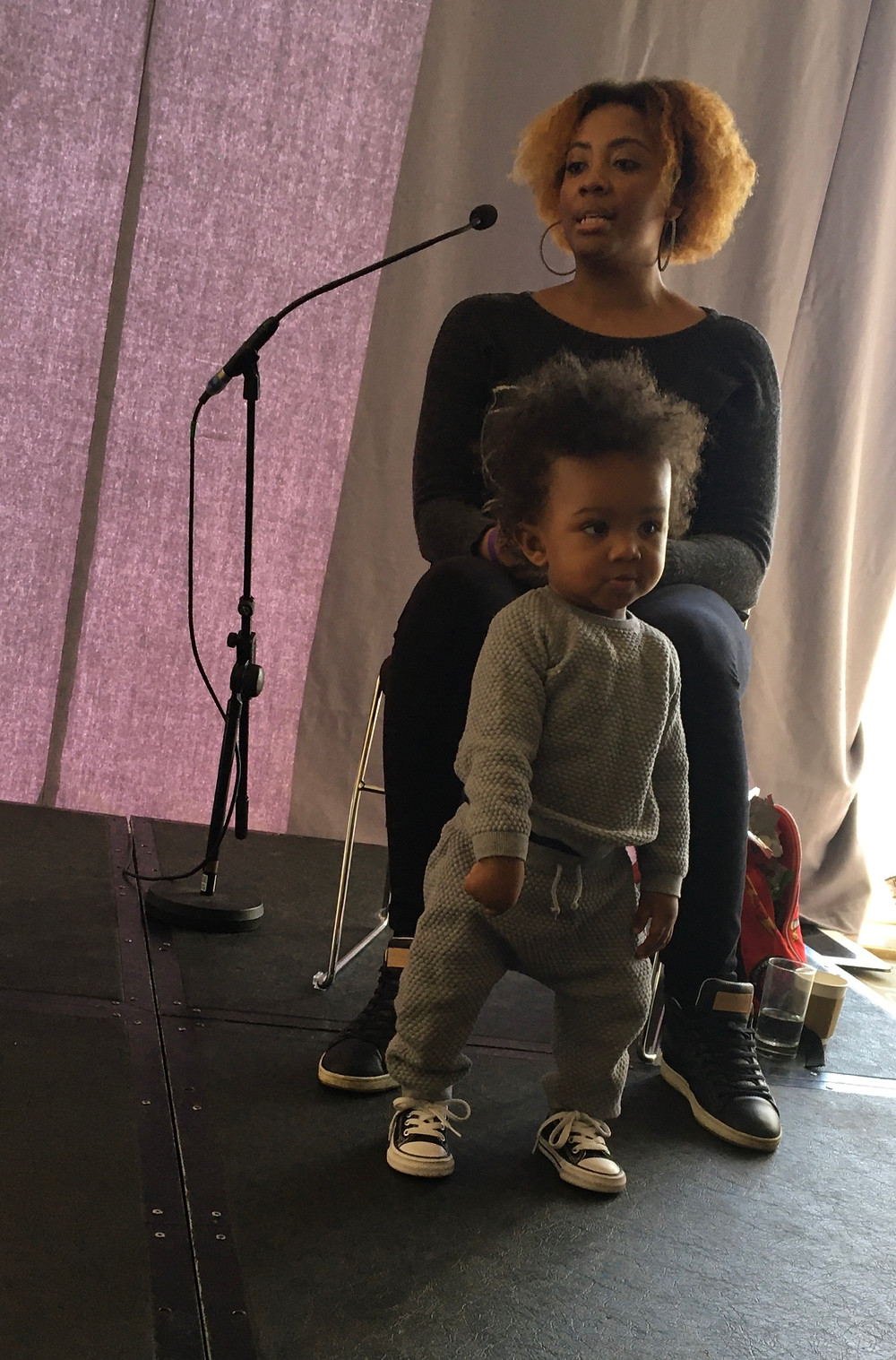 Jendella Benson in a chair with her one-year-old son standing in front of her smiling