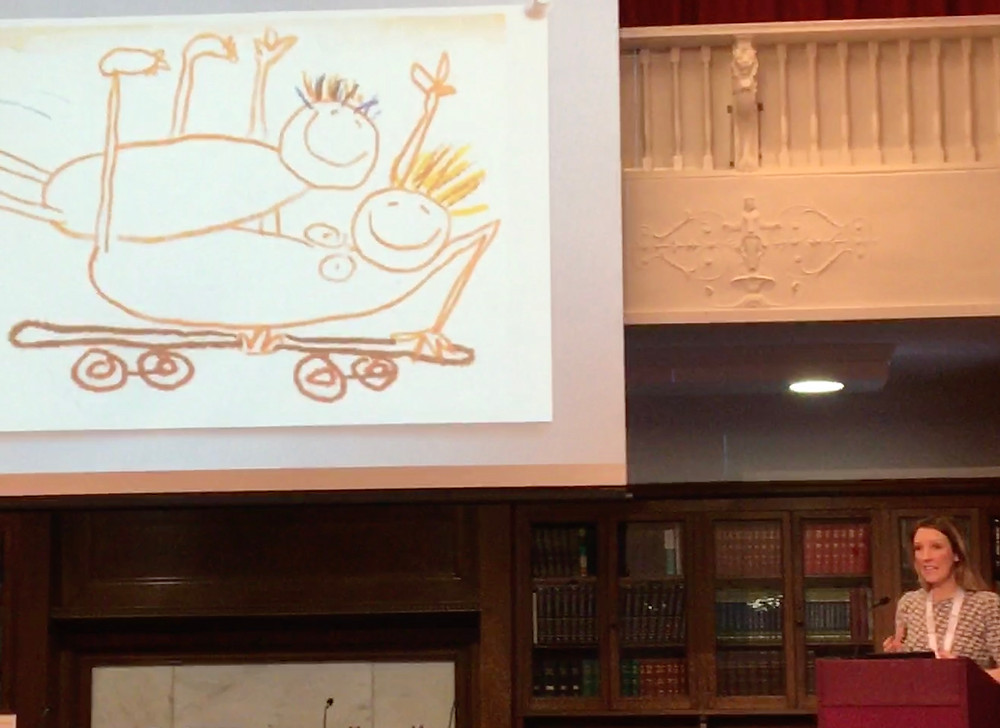 Rebecca Jennings in front of a slide showing a childlike drawing of a man on top of a woman on a skateboard!