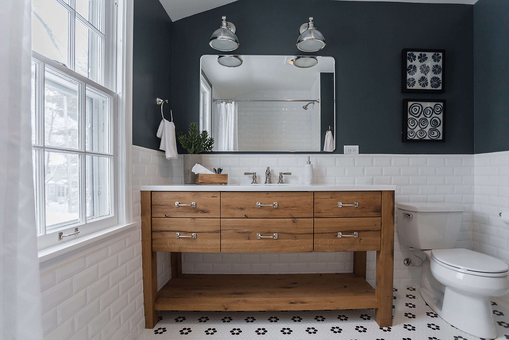 Custom reclaimed wood vanity with open bottom base, playful flower floor tile and deep teal walls